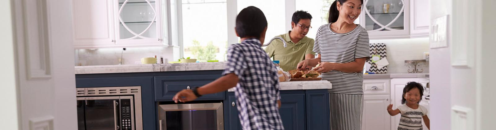 family in a kitchen smiling while two young children play