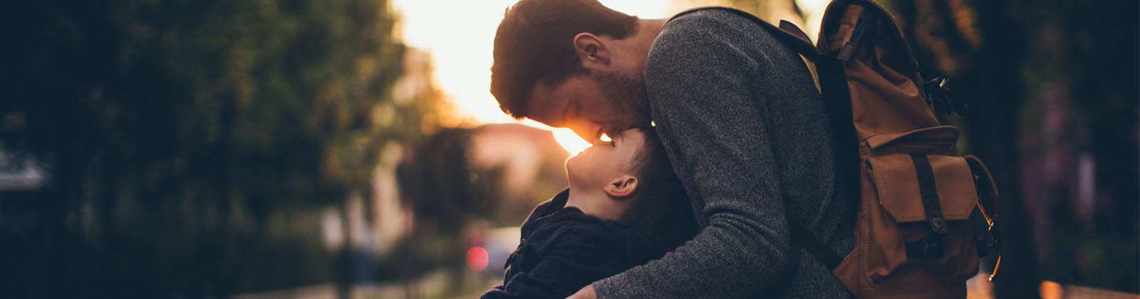 man kissing his son's forehead while outdoors