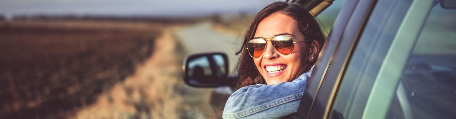 woman looking out her car window smiling