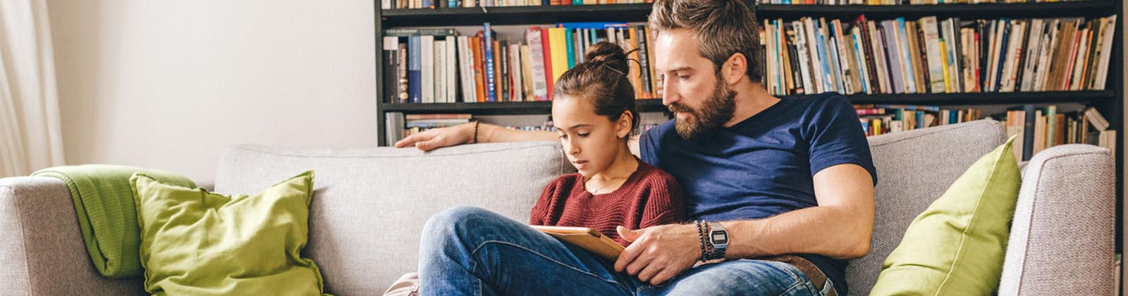 father and daughter reading on a couch together