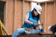 Advantis employee volunteering at the Habitat for Humanity, hammering nail.