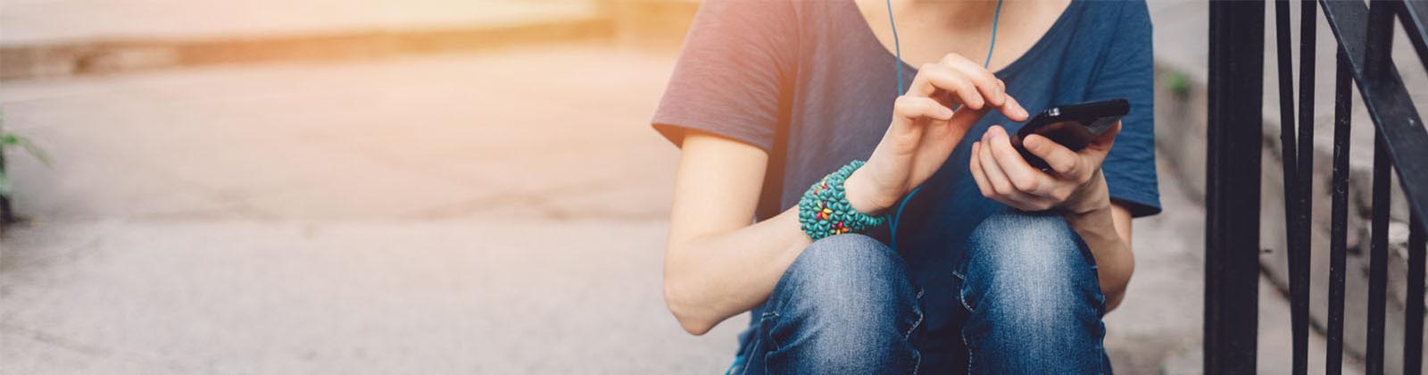 woman sitting on steps using a mobile device