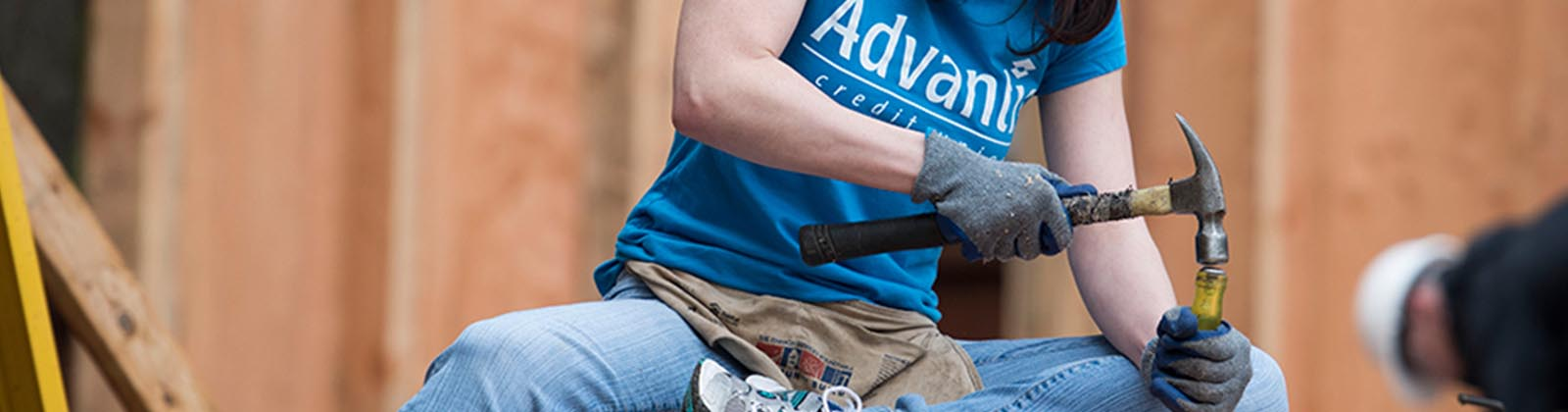 Advantis volunteer using a hammer while volunteering at Habitat for Humanity