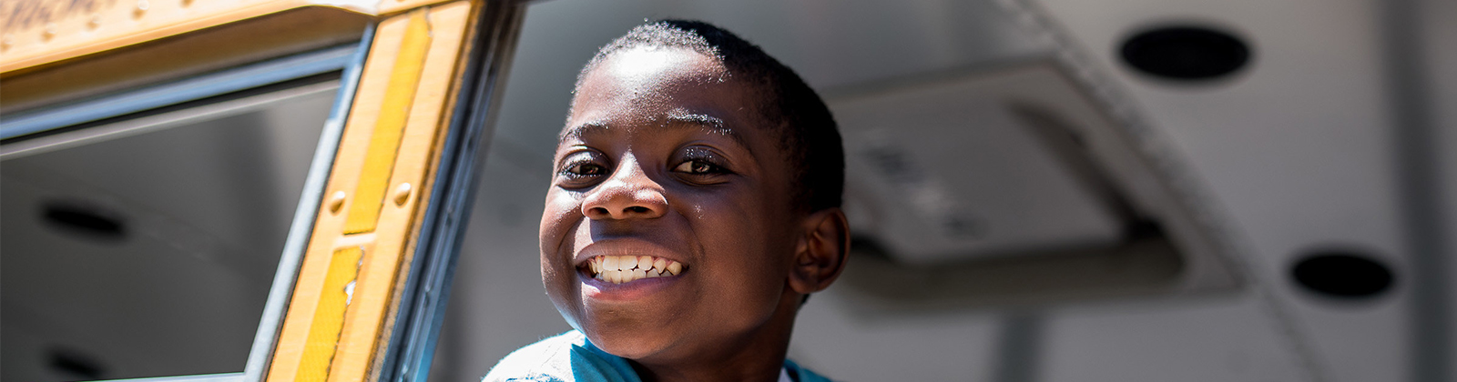 Child looking out bus window smiling